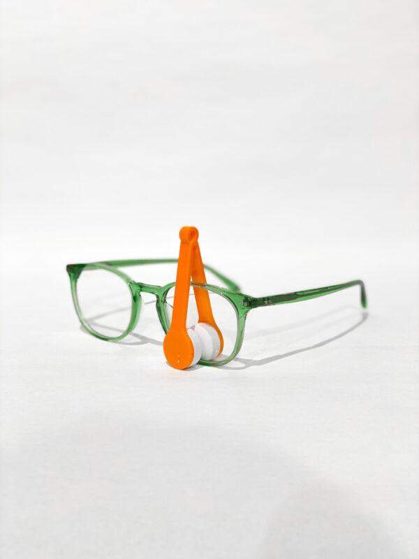 Oransje brillerens i bruk på briller med grøn innfatning