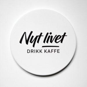 Hvit kaffebrikke med teksten Nyt Livet - Drikk Kaffe