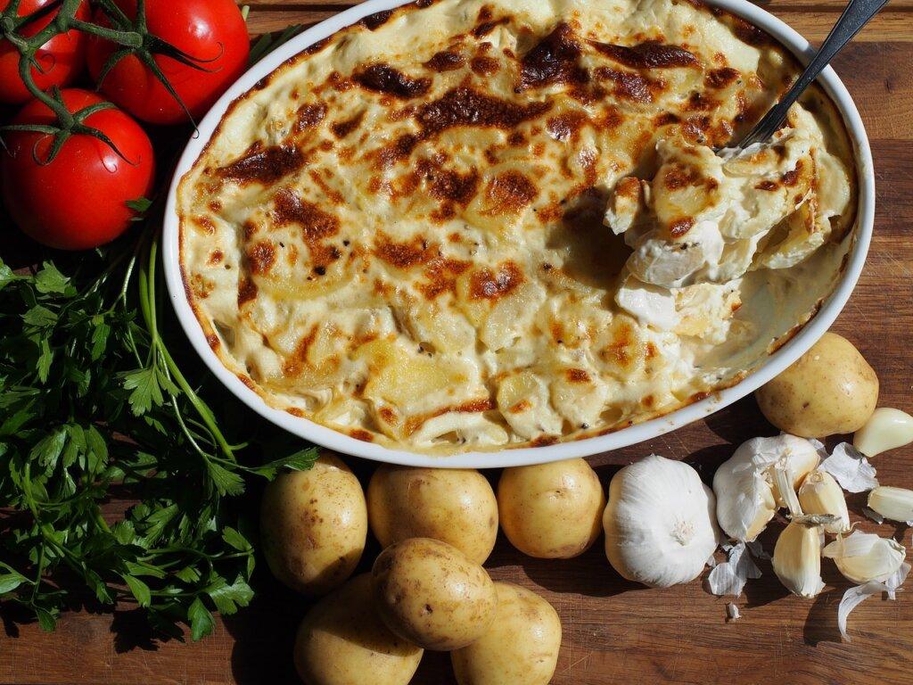 Fløtegratinerte poteter i rund form på et middagsbord omgitt av ferske grønnsaker og urter