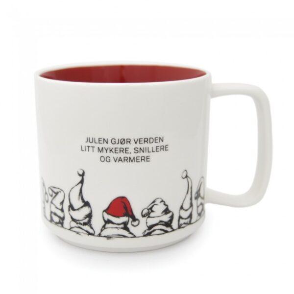 Hvit krus med rød innside og med teksten julen gjør verden litt mykere, snillere og varmere